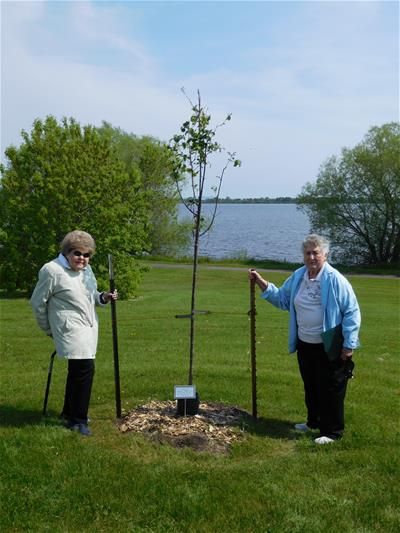 Marianne Peters and her friend, Hope Swenson, in front of their tribute tree.